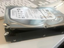 Prying open the broken drive, for use as a upcycled art-piece